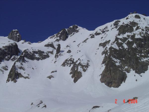 Sedlo před námi a ve svahu jsou vidět stoupající lyžaři.