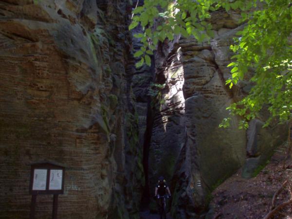 Projíždíme stezkou skrz skalní útvary, bylo tam šero.