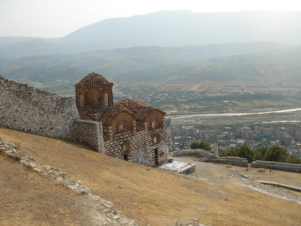 Zbytky byzantského kostela s městem v pozadí.