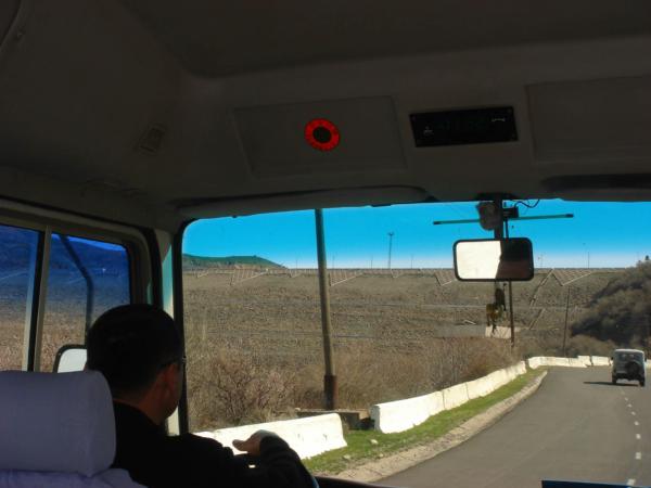 Přehradní hráz z okna autobusu se tyčí na městem Charvak.
