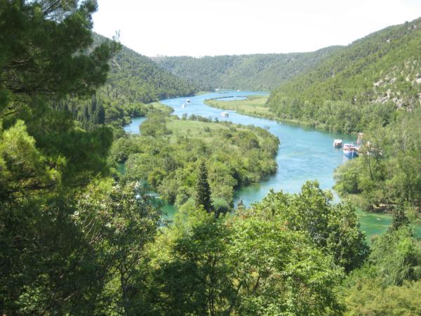Pohled na zákruty řeky Krka nad vodopády - a plno výletních lodí.