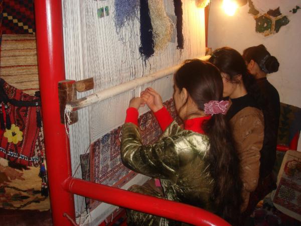 Uvnitř Sher Dor Medressy dámy tkají koberec.