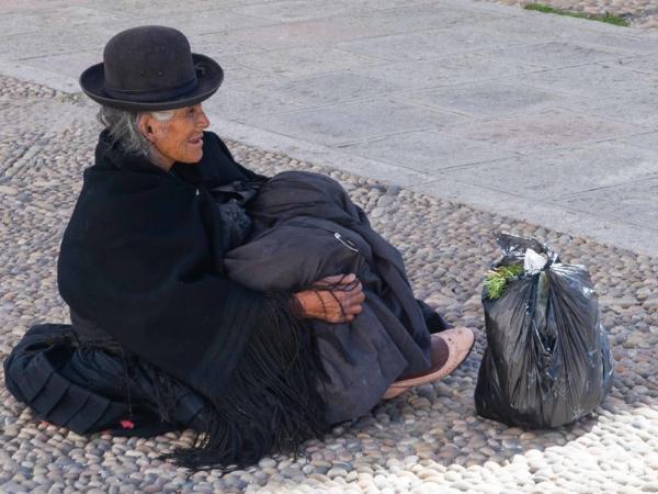 Odpočívající paní (žebračka?) u kostela.