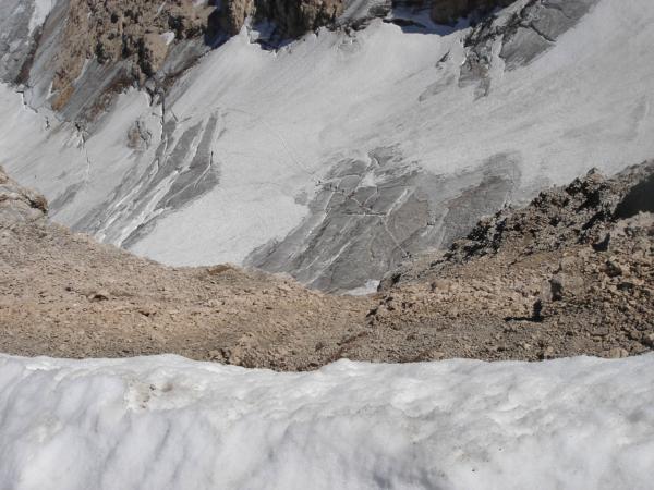 Pohled ze vrcholu stěnu dolů na pěšinku vedocí po ledovci.